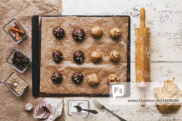 Cookie dough on baking sheet near rolling pin and ingredients