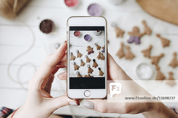 Hands of Caucasian woman photographing Christmas cookies with cell phone