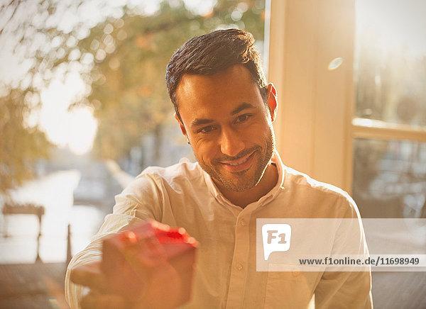 Persönliche Perspektive junger Mann schenkt im sonnigen Cafe