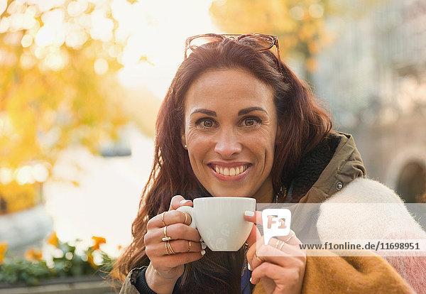 Portrait lächelnde Frau beim Kaffeetrinken im herbstlichen Straßencafé