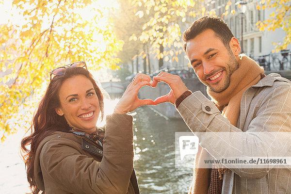 Portrait lächelndes junges Paar in Herzform mit Händen am sonnigen Herbstkanal