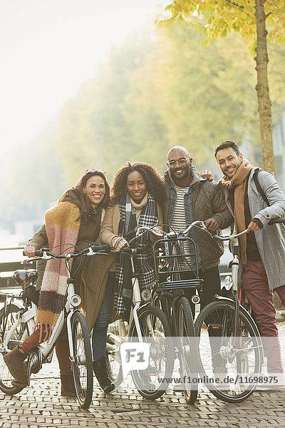 Portrait Freunde Radfahren auf urbaner Herbststraße