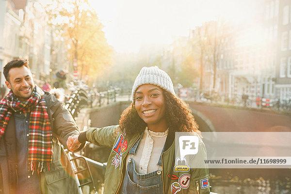 Porträt eines lächelnden jungen Paares am Kanal in Amsterdam
