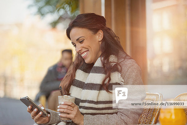 Lächelnde Frau beim SMSen mit Handy und Trinken von Milchshake im Straßencafé