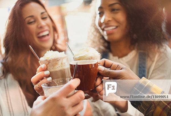 Lächelnde Freunde toasten Milchshakes und Kaffeetassen im Cafe