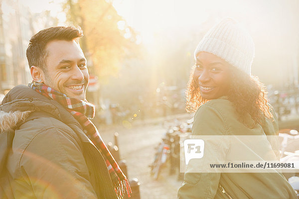 Portrait lächelndes junges Paar auf sonniger urbaner Herbststraße