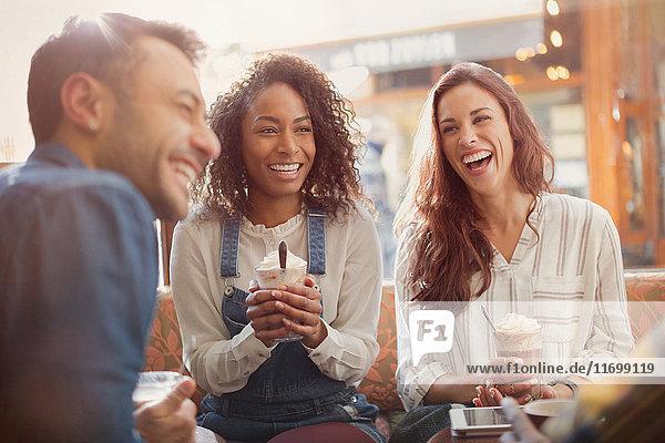 Lachende junge Freunde trinken Milchshakes im Cafe