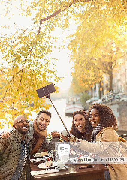 Lächelnde Freunde nehmen Selfie mit Selfie-Stick im herbstlichen Bürgersteig-Café