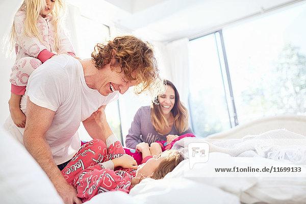 Familie lacht und spielt auf dem Bett