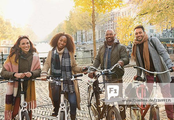Portrait lächelnde Freunde Radfahren in der urbanen Herbststraße  Amsterdam