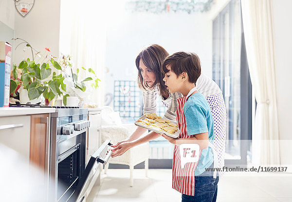 Mother and son baking  placing cookies in oven in kitchen