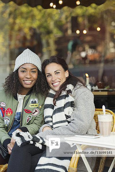 Portrait lächelnde junge Frauen Freunde in warmer Kleidung auf dem Bürgersteig Cafe