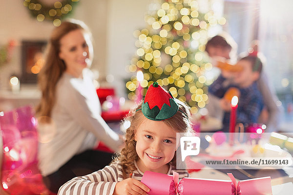 Portrait smiling girl holding Christmas cracker at dinner table