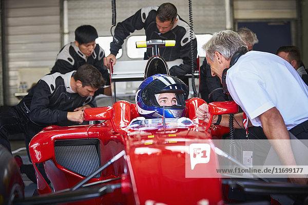 Manager im Gespräch mit Formel-1-Rennfahrer in der Werkstatt
