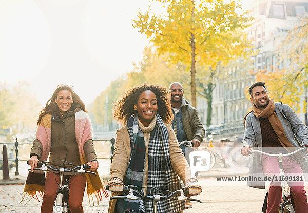 Lächelnde junge Freunde beim Radfahren auf der urbanen Herbststraße