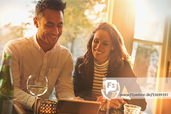 Junges Paar trinkt Wein und benutzt Tablet PC im sonnigen Restaurant