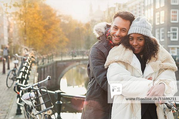 Portrait lächelndes junges Paar in warmer Kleidung am Kanal in Amsterdam