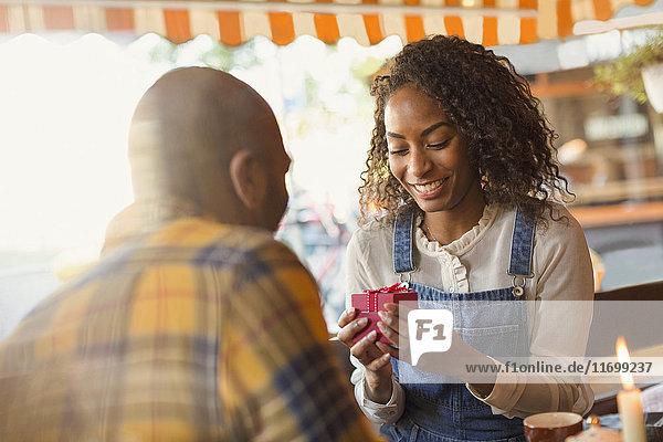 Junger Mann schenkt Freundin im Cafe