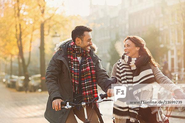 Lächelndes junges Paar in warmer Kleidung Fahrrad fahren auf urbaner Herbststraße