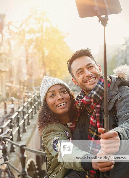Lächelndes junges Paar  das Selfie mit Selfie-Stick auf der Straße nimmt.