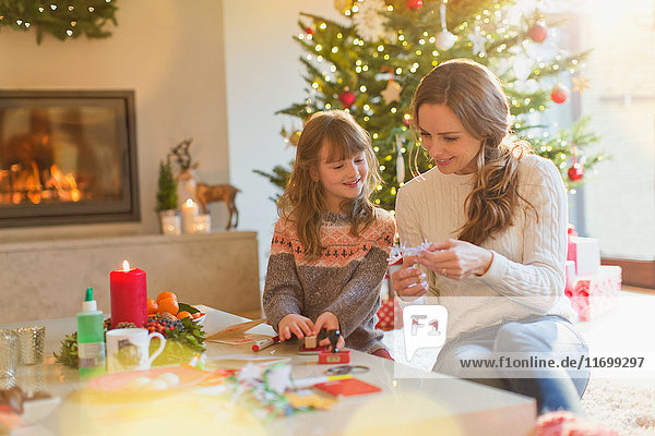 Mother and daughter making Christmas snowflake decorations in living room
