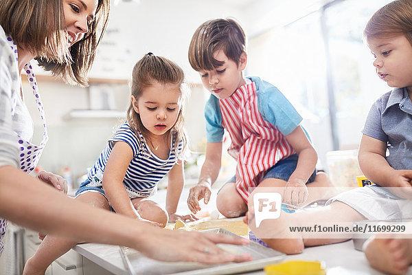 Mutter und Kinder beim Backen in der Küche