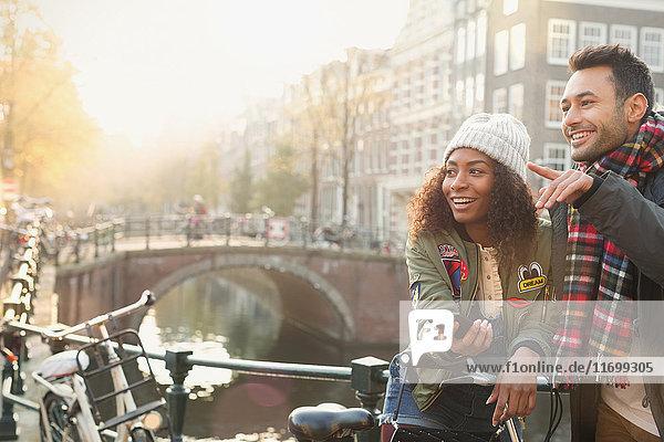 Junges Paar mit Fahrrädern auf der Stadtbrücke über den Kanal  Amsterdam