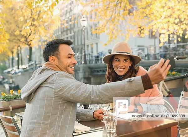 Junges Paar nimmt Selfie mit Fotohandy im herbstlichen Bürgersteig-Café