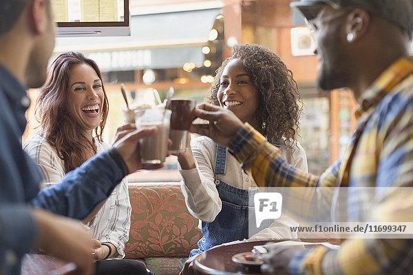 Lächelnde Freunde toasten Kaffeetassen im Cafe