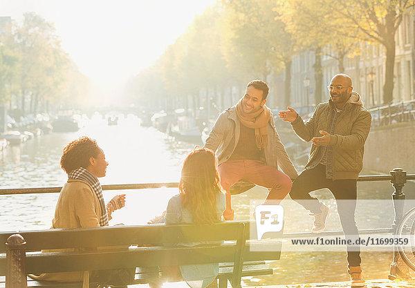 Junge Freunde beim Reden  auf der sonnigen städtischen Herbstbrücke über den Kanal  Amsterdam