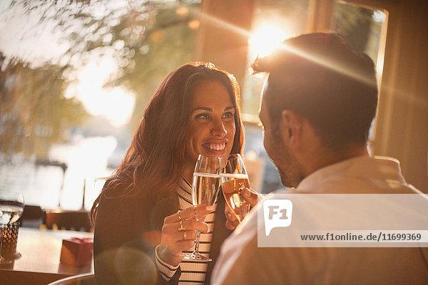 Zärtliches junges Paar  das im Restaurant Champagnergläser anstößt