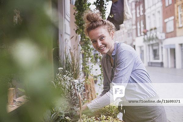 Portrait smiling young female florist arranging display at storefront