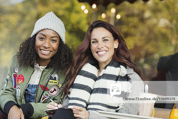 Portrait lächelnde junge Frauen Freunde schreiben Postkarte auf dem Bürgersteig Cafe
