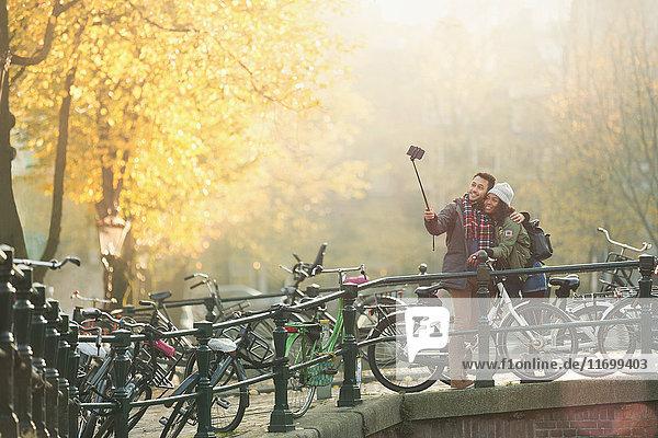 Junges Paar mit Fahrrädern nimmt Selfie mit Selfie-Stick auf der Herbstbrücke  Amsterdam