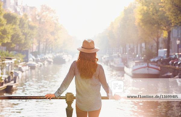 Frau mit Hut mit Blick auf den sonnigen Herbstkanal  Amsterdam