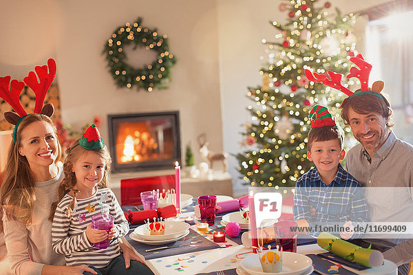 Portrait smiling young family wearing costume reindeer antlers at Christmas dinner table