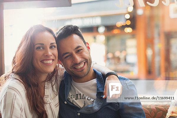 Portrait glückliches junges Paar beim Umarmen im Cafe