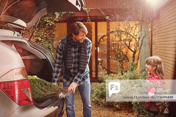 Vater und Tochter beim Entladen des Weihnachtsbaums aus dem Auto außerhalb des Hauses