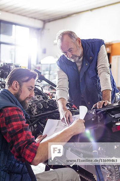 Motorradmechaniker prüfen Pläne in der Werkstatt