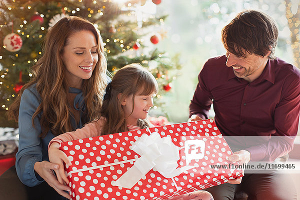 Parents giving large Christmas gift to daughter in front of Christmas tree