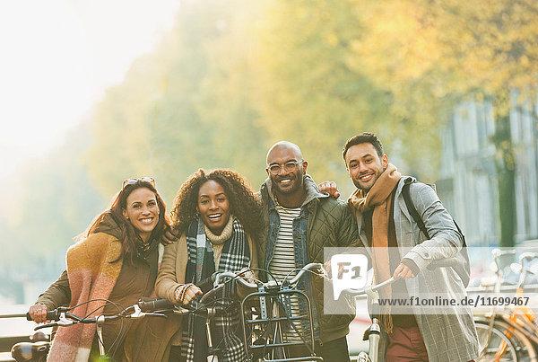 Portrait lächelnde Freunde Fahrrad fahren auf städtischer Herbststraße