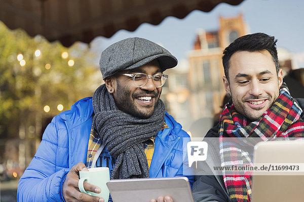 Lächelnde junge Männer Freunde  die Kaffee trinken und Laptop und digitales Tablett im Straßencafé benutzen.