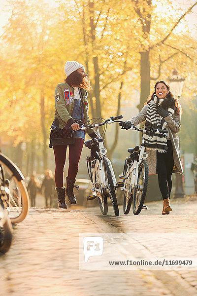 Junge Frauen  die mit dem Fahrrad durch die sonnige Herbststraße laufen.