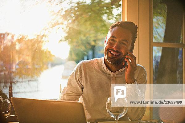 Lächelnder junger Mann beim Telefonieren und Laptopbenutzung im sonnigen Café