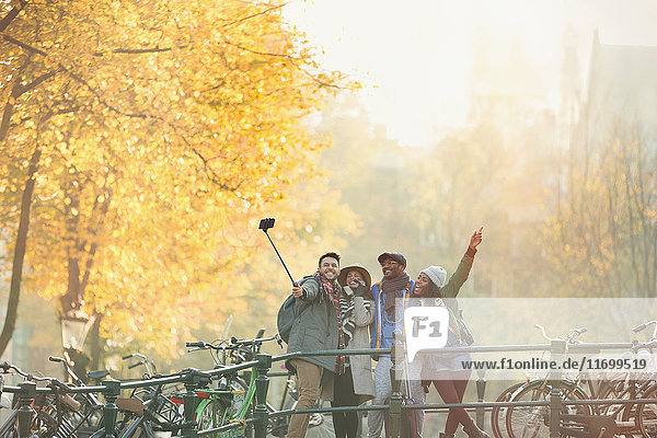 Verspielte junge Freunde nehmen Selfie mit Selfie Stick auf urbaner Herbstbrücke  Amsterdam