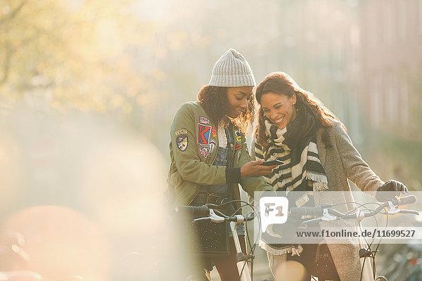 Junge Freundinnen mit Fahrrädern auf dem Handy in der sonnigen Herbststraße