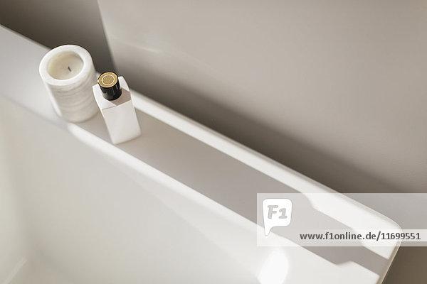 Candle and bottle casting shadow on ledge of white bathtub