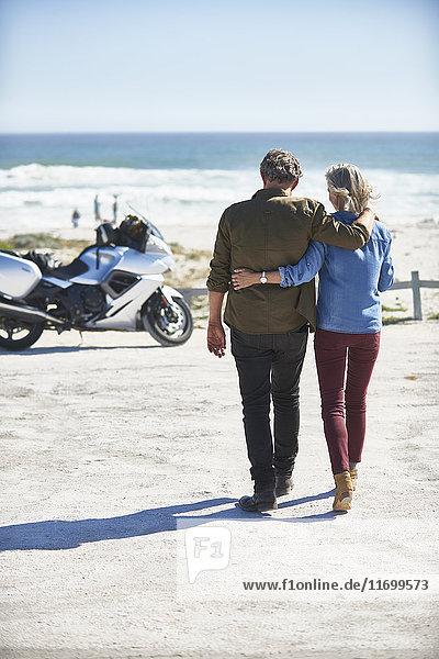 Liebevolles Seniorenpaar  das am sonnigen Strand zum Motorrad läuft