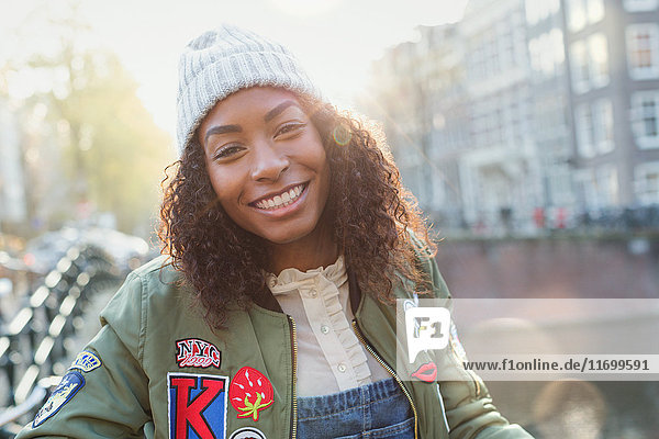 Portrait smiling young woman on sunny urban autumn street