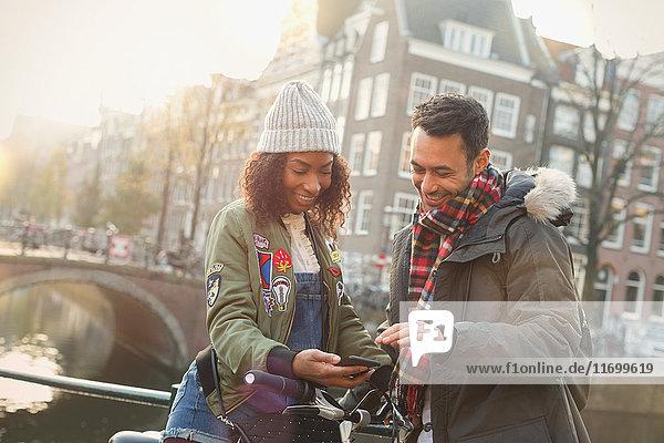 Junges Paar mit Fahrrad auf der Stadtbrücke  Amsterdam